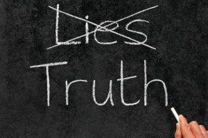 Crossing out Lies and writing Truth on a blackboard.